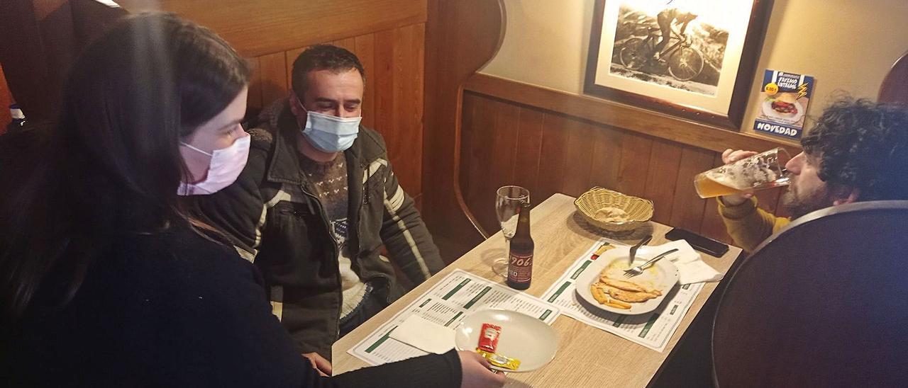 Asenet García sirve a Miguel Somoano (a la derecha) y a Ismael Sánchez, ayer en el interior de una hamburguesería de Posada de Llanes. | E. S. R.
