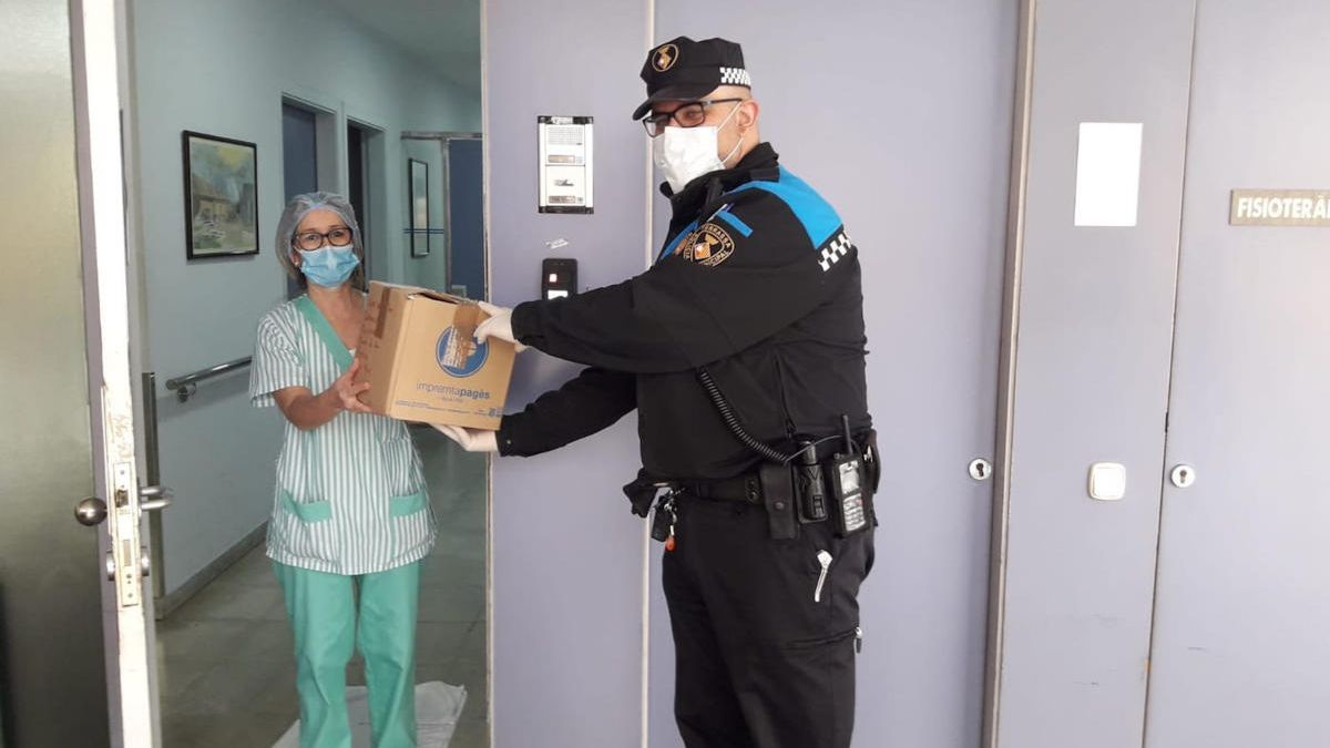 Un efectiu de la Policia Municipal reparteix material de protecció a residències de gent gran.