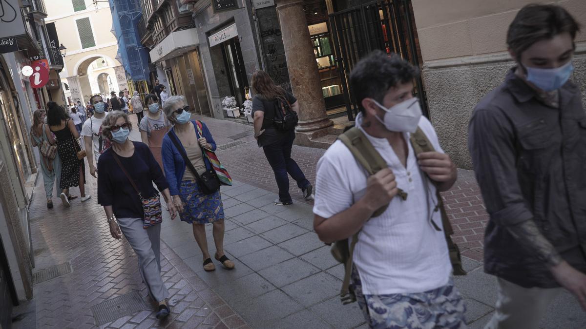 Ciudadanos pasean con mascarilla por la calle Sant Miquel de Palma