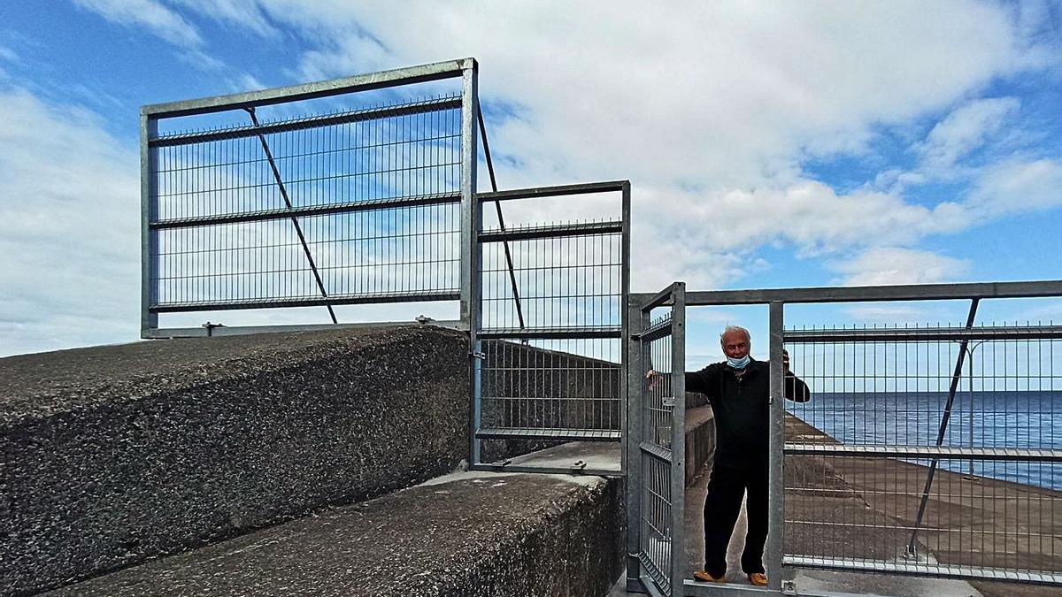 Anselmo Hulton, presidente de la asociación vecinal de San Esteban, junto a una de las vallas instaladas en el dique, en una imagen del pasado marzo. | S. Arias