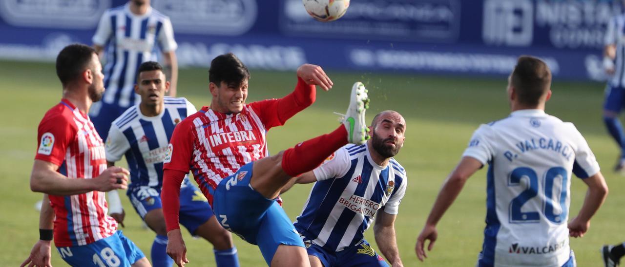 Cristian Salvador despeja un balón ante Javi Fuego en el Ponferradina-Sporting