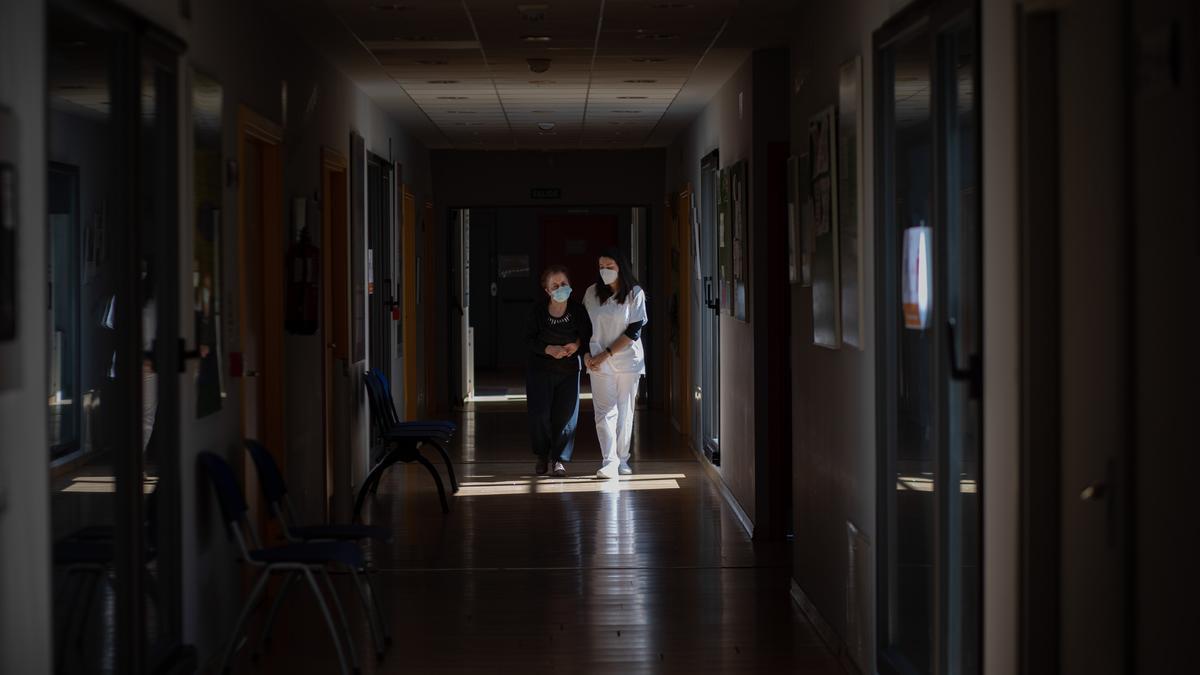 Una trabajadora camina con una de las usuarias por el pasillo del centro Ciudad Jardín de AFA Zamora. | Emilio Fraile