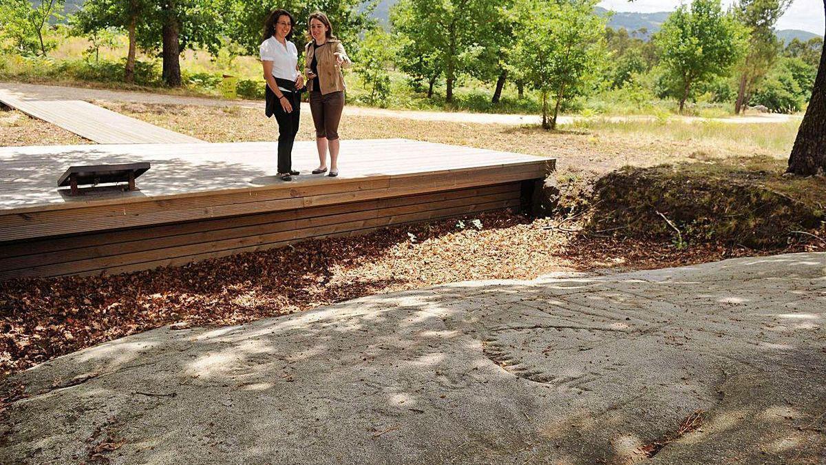Dos personas observan un petroglifo en el parque de Arte Rupestre de Campo Lameiro.