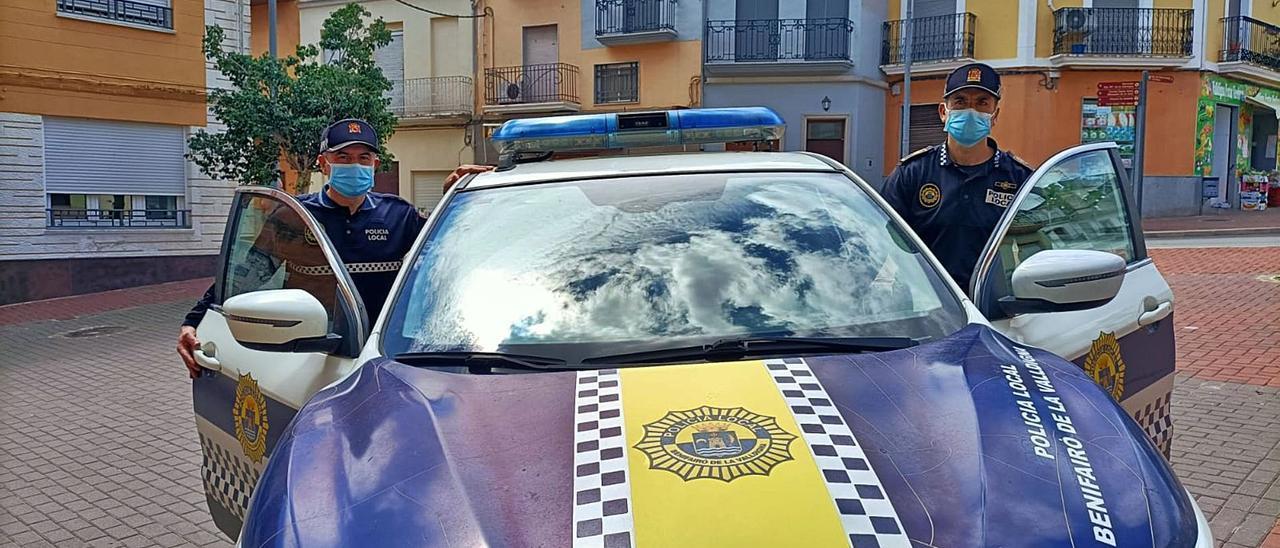 Un agente de Simat y otro de Benifairó suben al coche patrulla, ayer ante el consistorio simatero. | LEVANTE-EMV