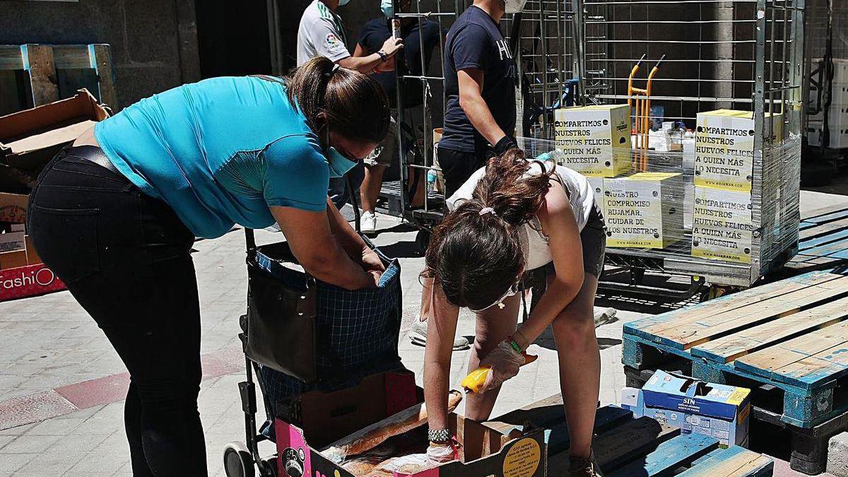Dos mujeres recogen alimentos de una caja durante una acción social.