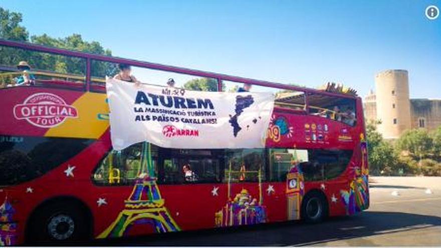 Tourismusgegner protestieren mit Transparent an einem Bus am Bellver-Schloss
