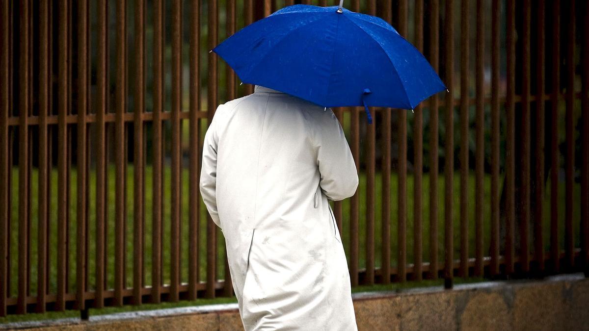 Un hombre pasea bajo la lluvia.