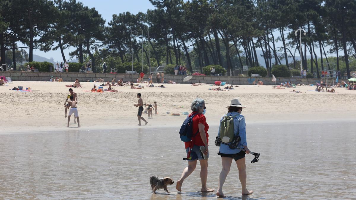 Dos personas y su perro pasean por la orilla de la playa de Samil