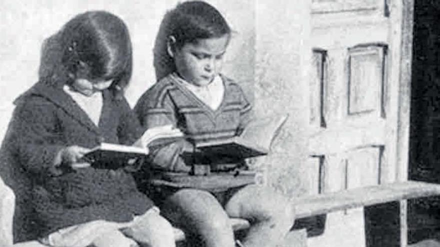 Niños leyendo en una foto antigua.