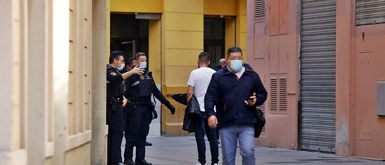Dos agentes dialogan con un hombre en la calle Viana. | M.A.MONTESINOS