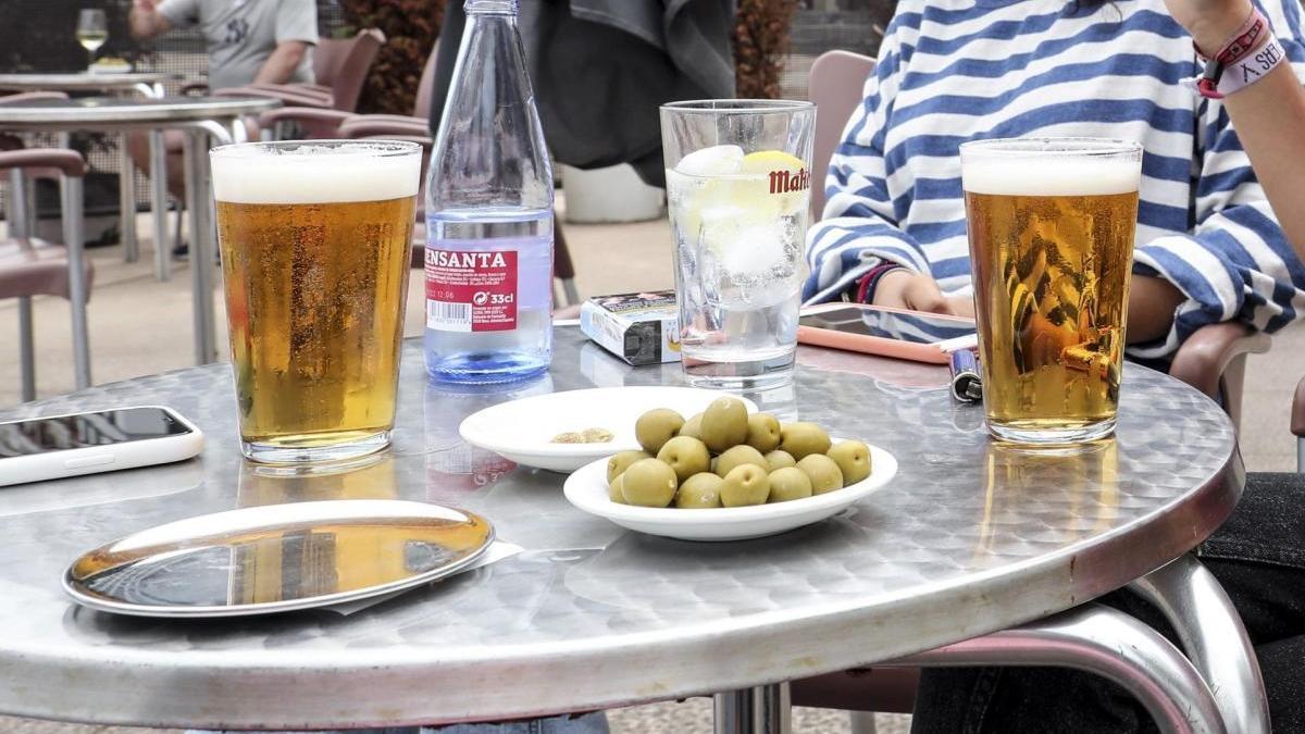 Dos jóvenes tomando cerveza en una terraza de un bar en una imagen de archivo.