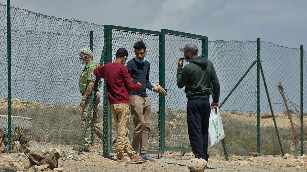 Un grupo de inmigrantes, en el exterior del campamento de El Matorral, en Fuerteventura, donde se ha detectado un enfermo por coronavirus.