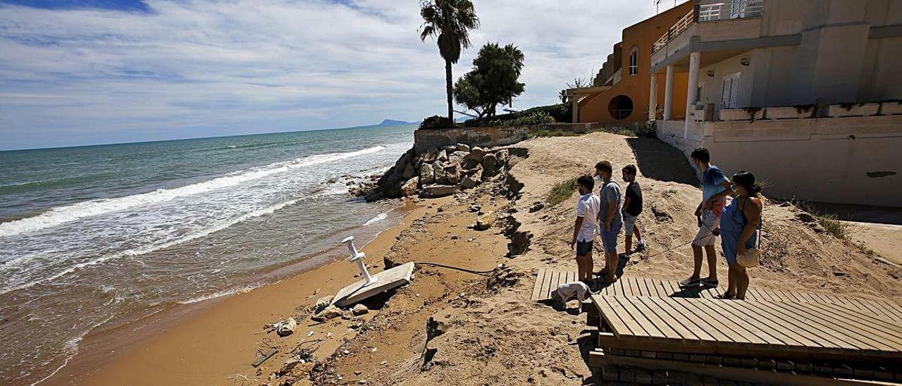 Un grupo de personas observa los destrozos que el último temporal ha causado en la playa de la Goleta de Tavernes, donde las olas rompen en las casas.