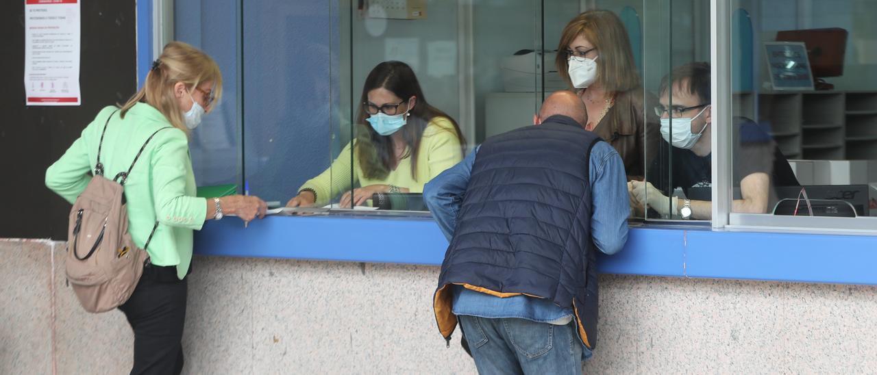Funcionarios en una ventanilla de atención al público.