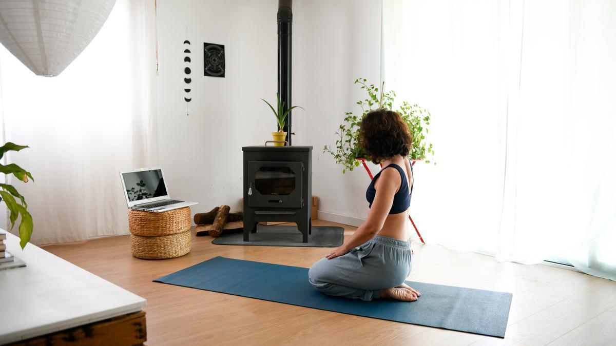 Pla general d'una usuària de Tramuntana Yoga seguint una classe penjada a la plataforma