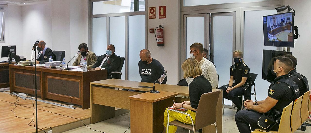 Los dos acusados en el banquillo con la intérprete y custodiados por la Policía el primer día del juicio. | HÉCTOR FUENTES