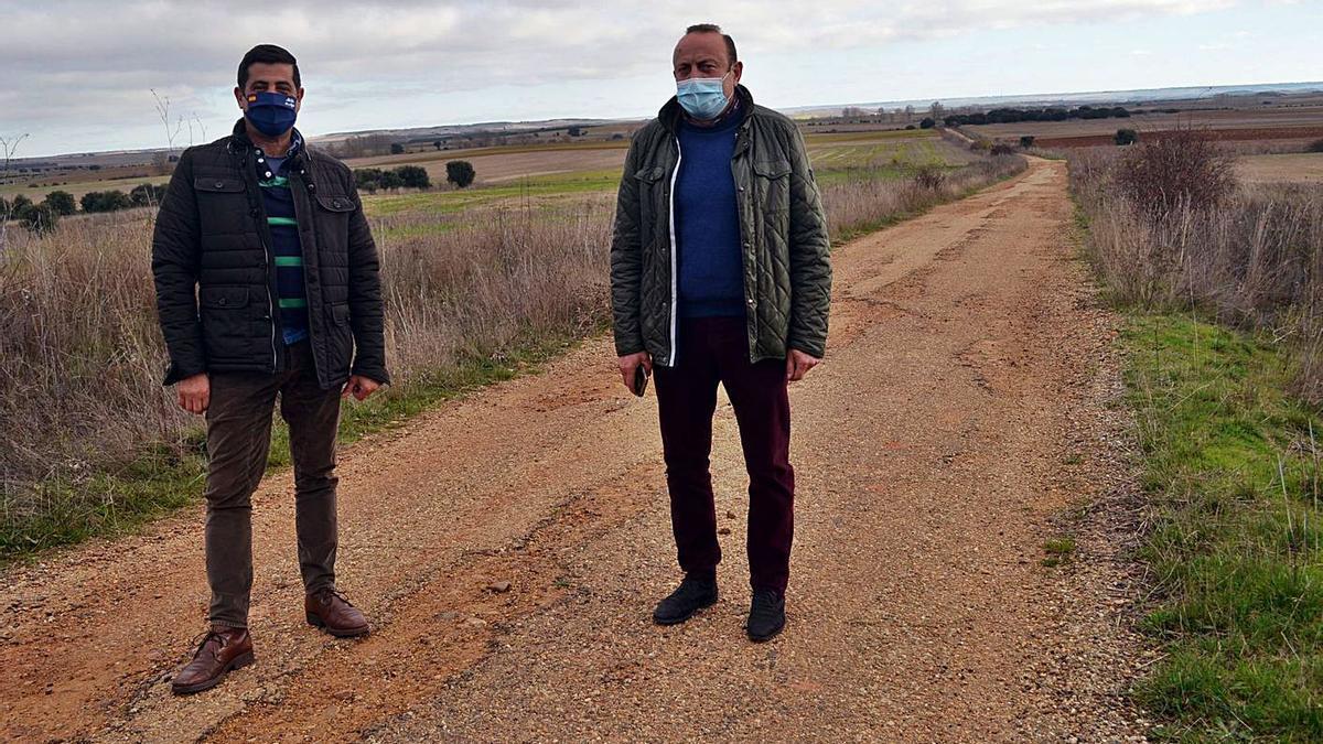 Los alcaldes de Pobladura (derecha) y Matilla (izquierda) muestran el estado del camino agrícola. | E. P.
