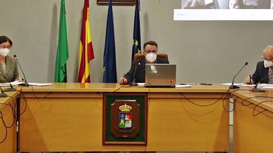 El alcalde en funciones, Javier González, con los dos funcionarios en el salón de plenos, y el resto de la Corporación, en la pantalla.
