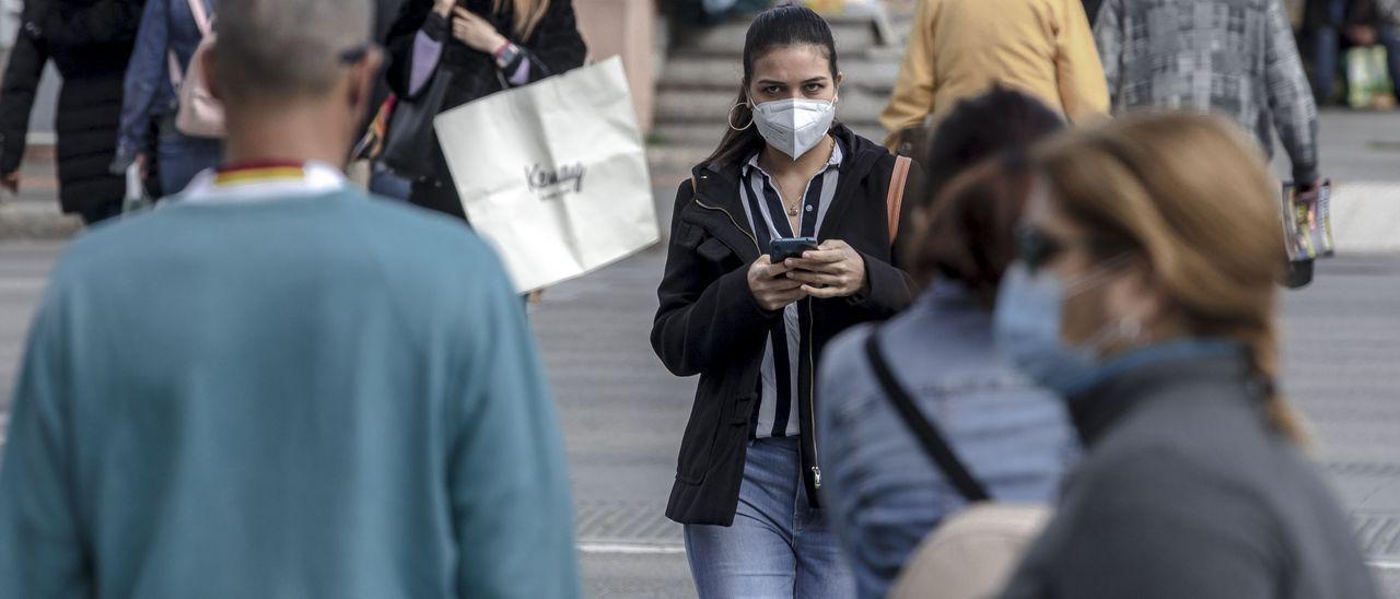 Una joven anda co la mascarilla por la calle, en una imagen de archivo.