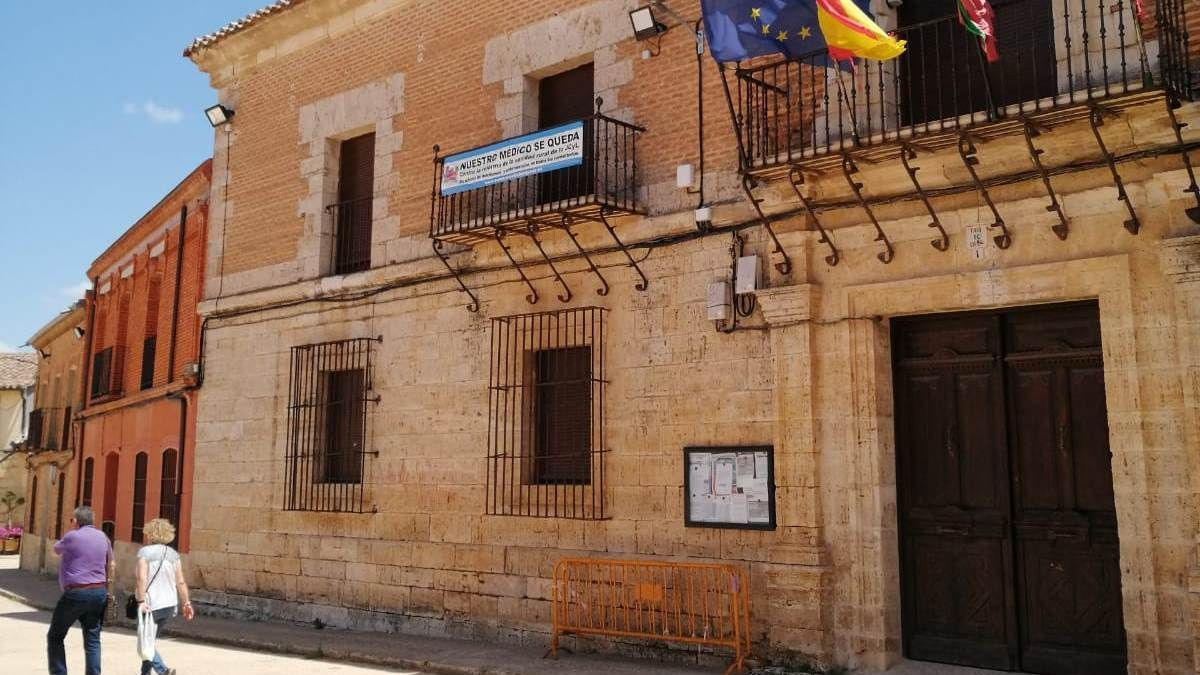 Dos vecinos pasean por la plaza en la que está enclavado el Ayuntamiento de Morales de Toro