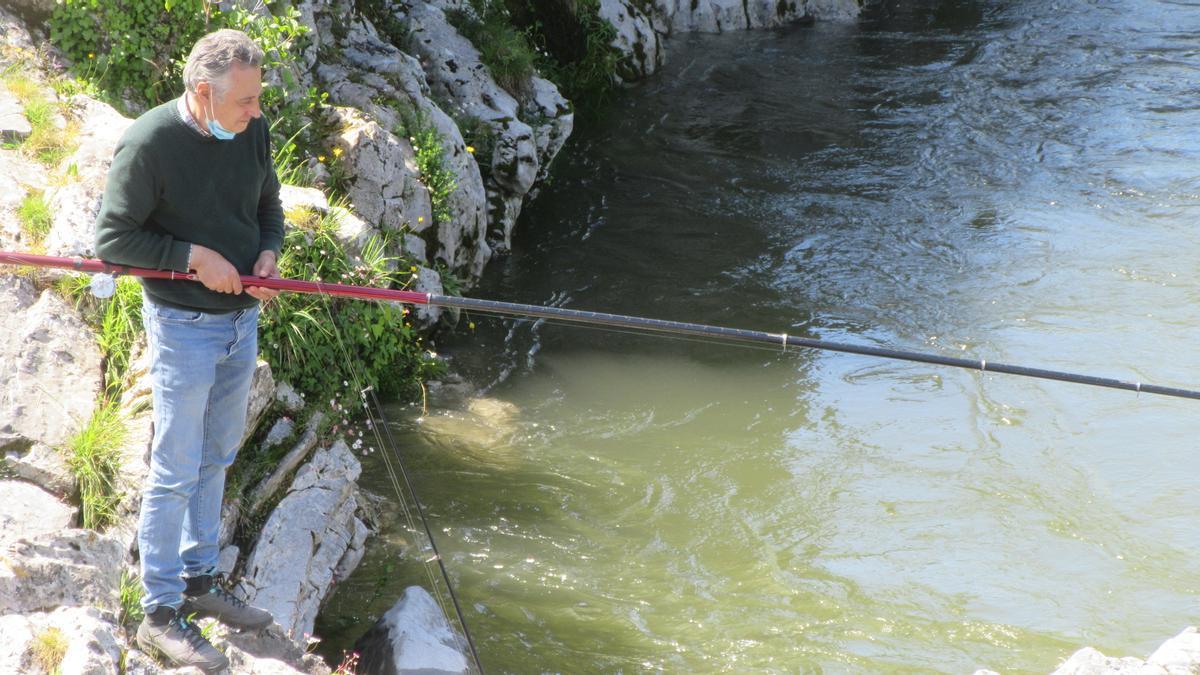 Un ribereño pescando en el Sella, muy turbio.