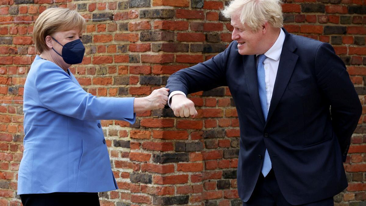 Merkel y Johson se saludan.