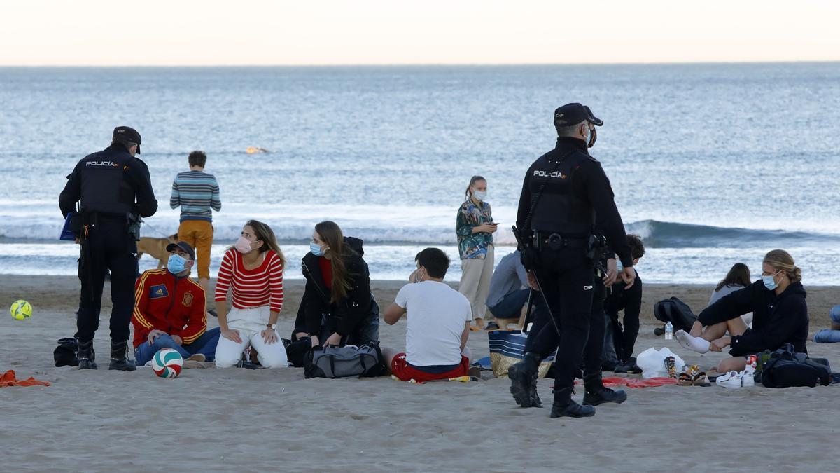 Policías nacionales recorren la playa para prevenir botellones y hacer cumplir la normativa covid.