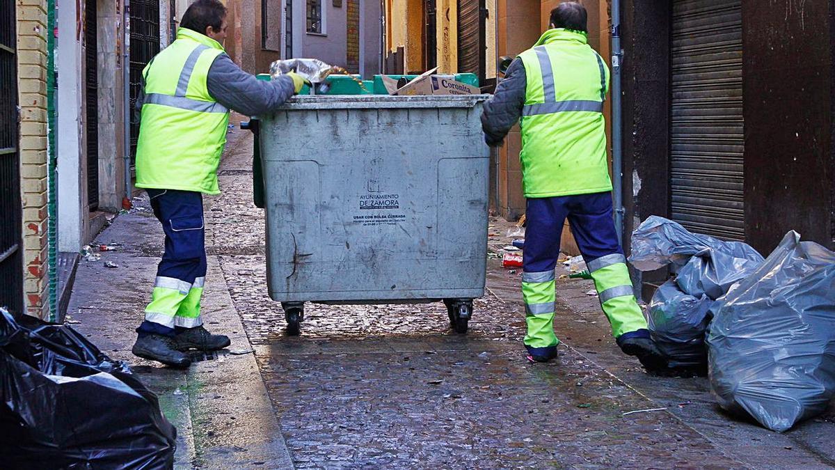 Dos trabajadores de la limpieza empujan un contenedor por la calle de los Herreros.