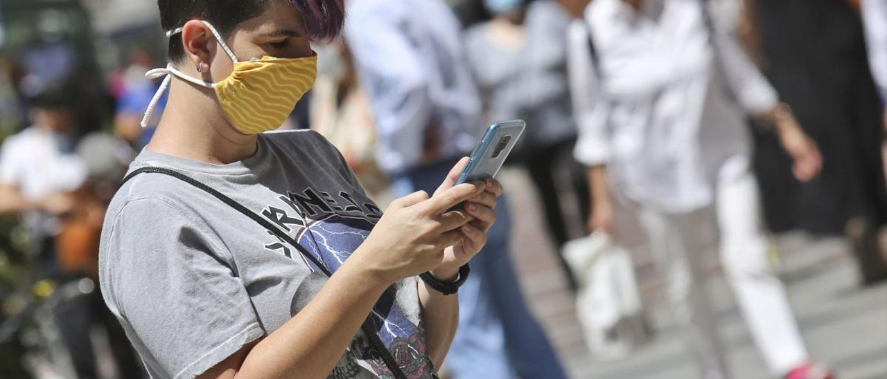 Una mujer con una mascarilla escribiendo por el móvil en Oviedo