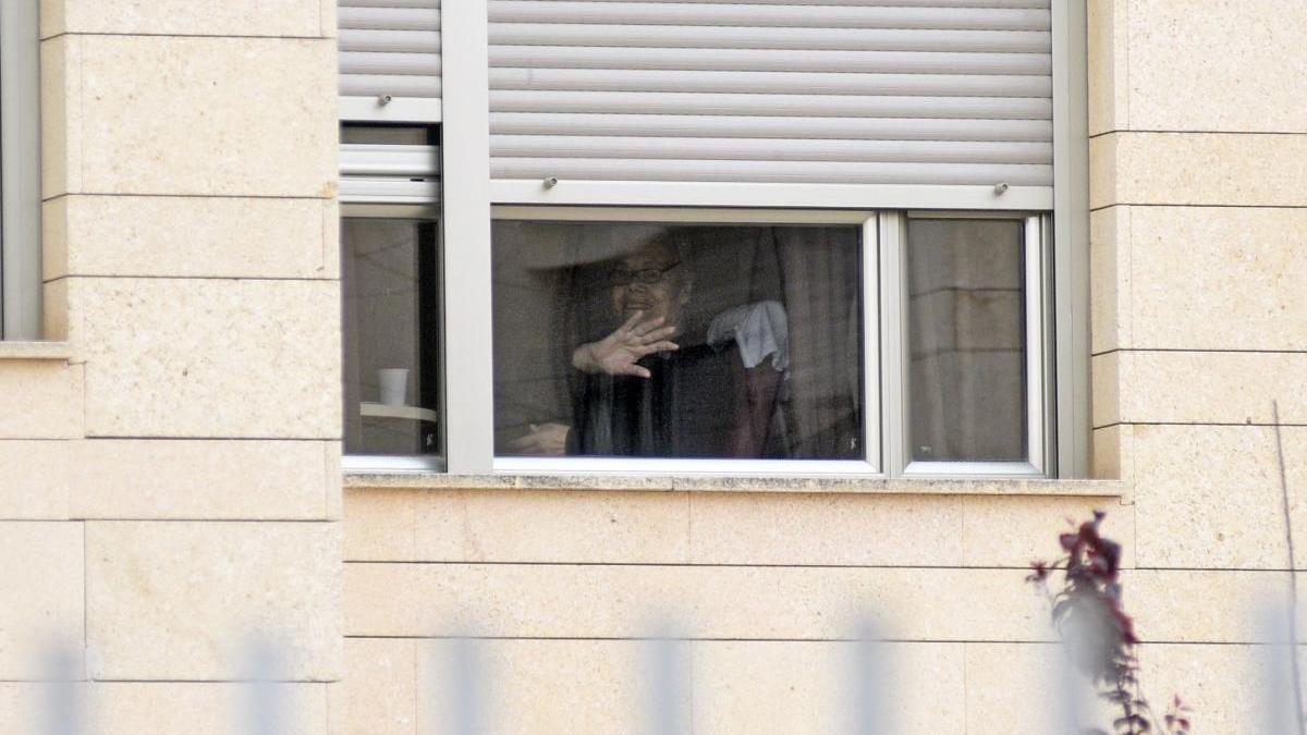 Una persona desde una ventana de una residencia de Santomera.