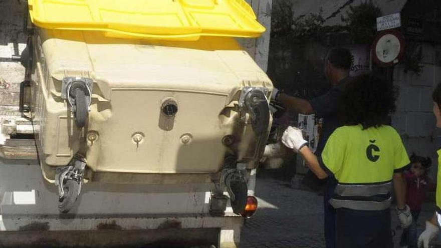 Una empleada de Cespa vacía un contenedor en un camión.