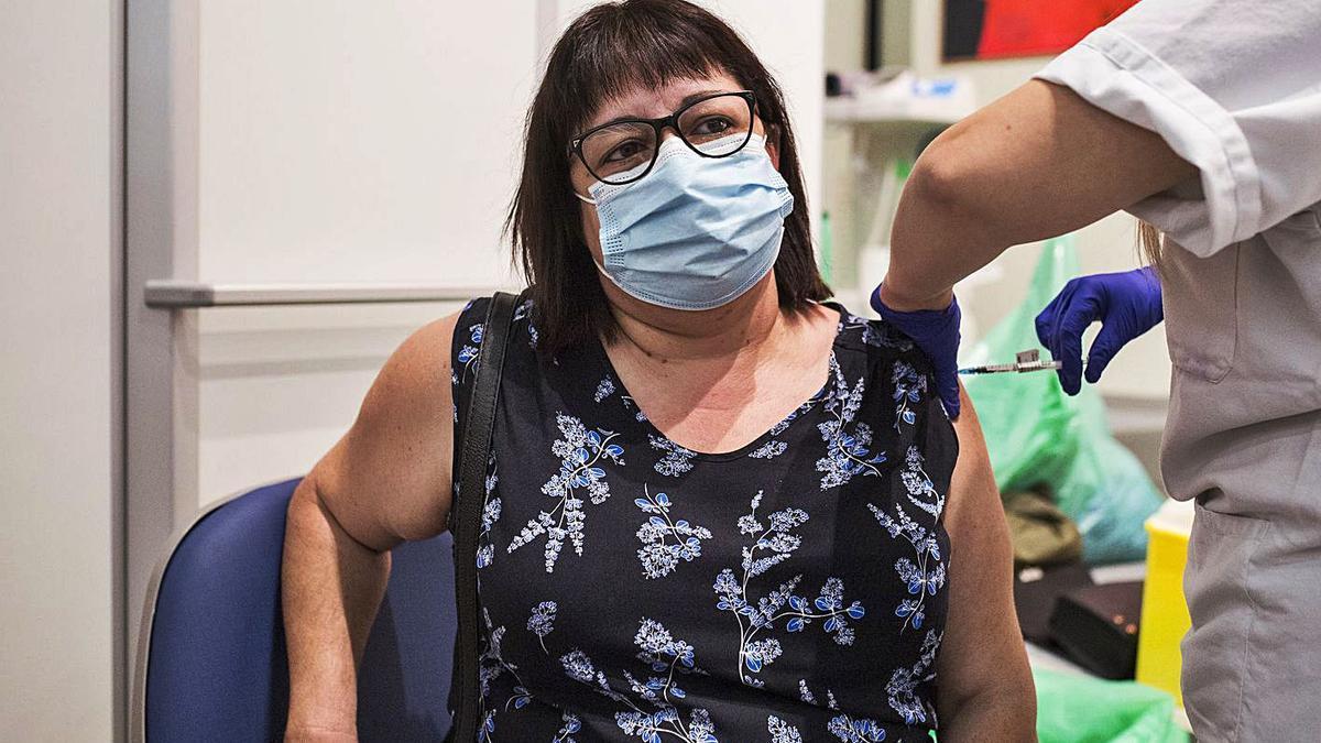 Una sanitaria administra a una mujer una vacuna de Pfizer, ayer en Madrid.   ALEJANDRO MARTÍNEZ VÉLEZ / EP