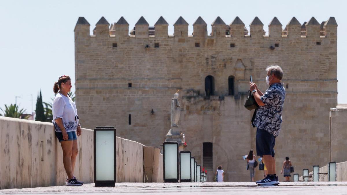 Unos turistas se hacen una foto en el Puente Romano.
