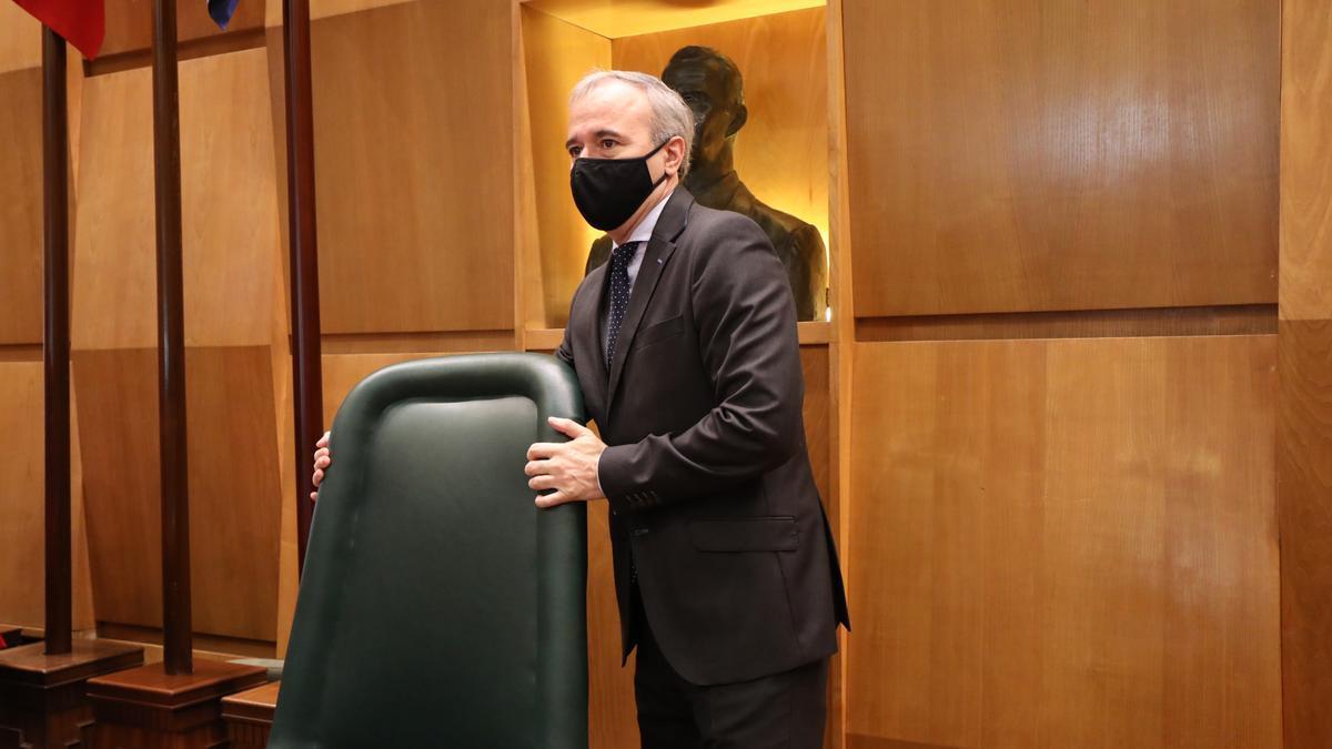 El alcalde de Zaragoza, Jorge Azcón, se dispone a sentarse en su butaca, ayer, minutos antes del pleno del Ayuntamiento de Zaragoza.