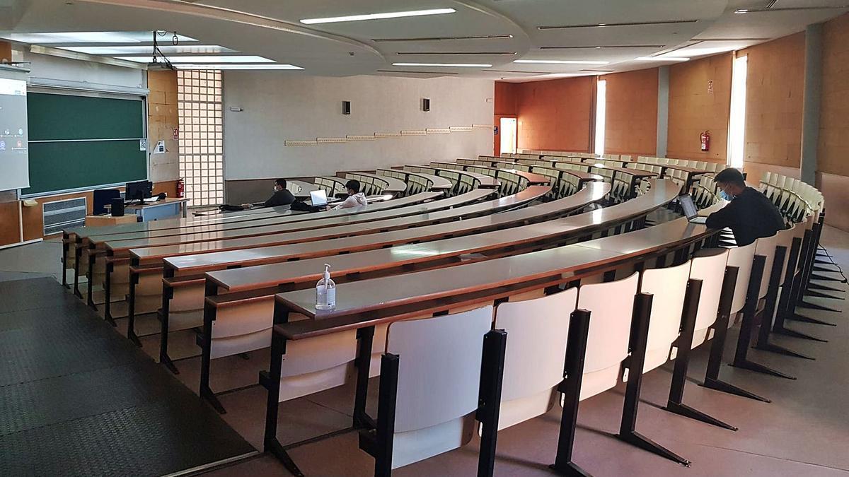 Clase semipresencial de introducción a la microeconomía, en el Aulario 1 de la UA, con la pantalla virtual a la izquierda de la pizarra.