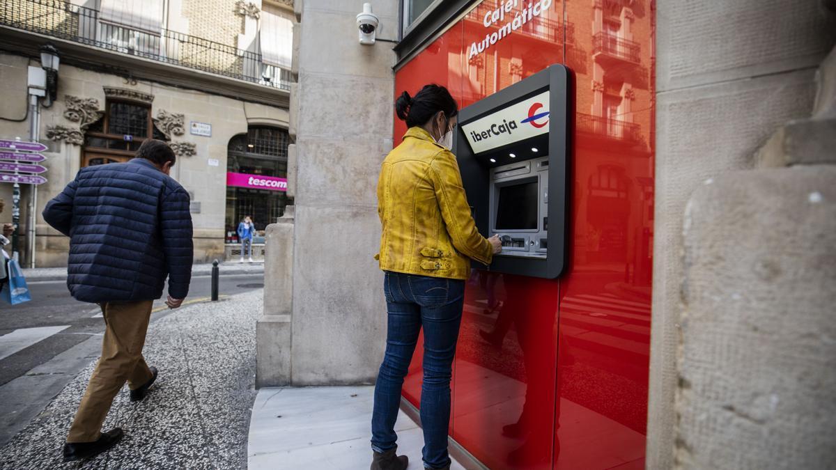 Una mujer saca dinero de un cajero automático en Zaragoza.