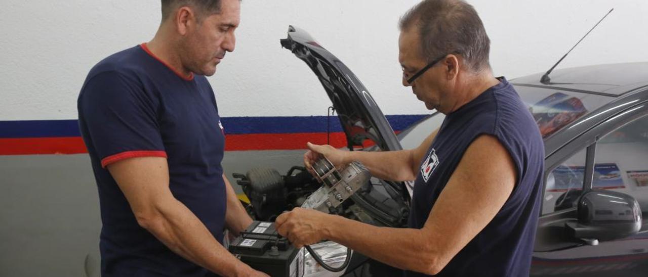 Dos mecánicos reparan una batería en un taller del centro de Alicante.