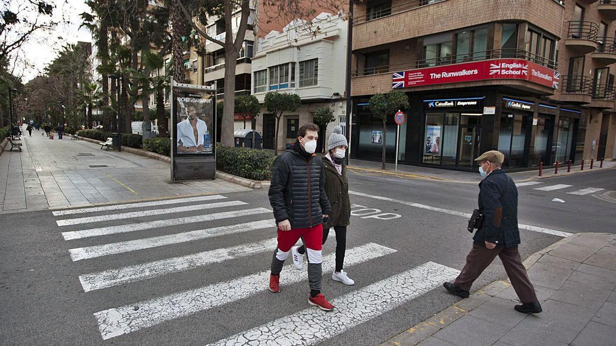 Una pareja camina por la avenida de Torrent, localidad afectada por el cierre perimetral. | F. BUSTAMANTE