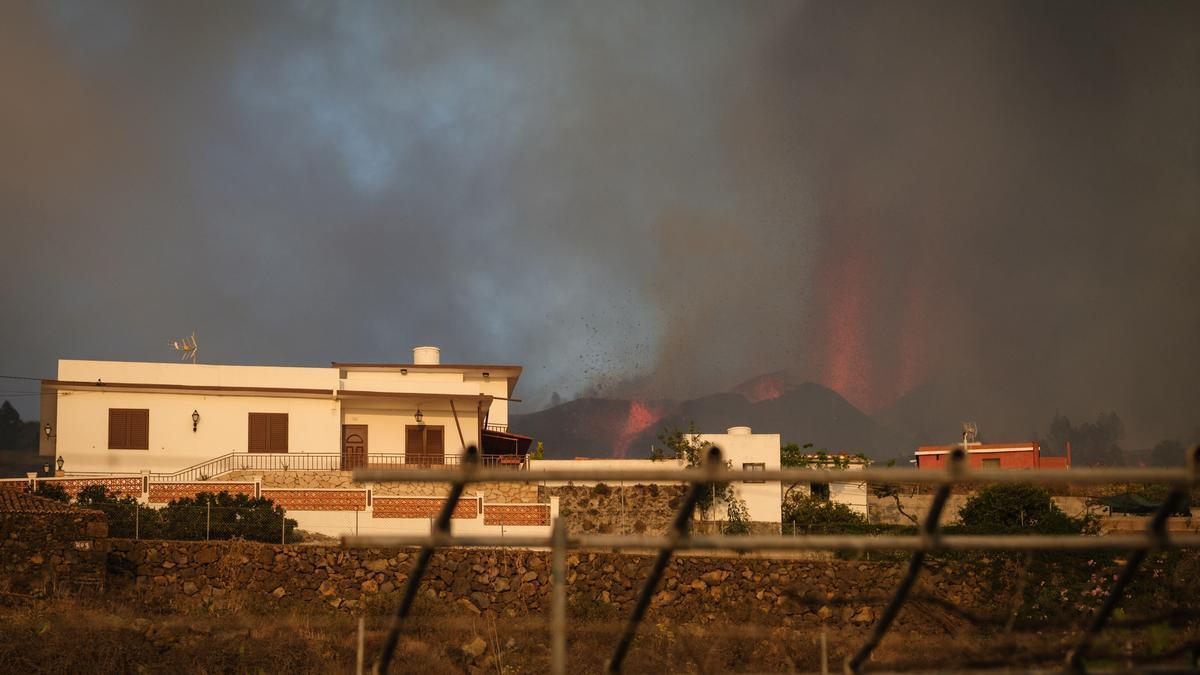 El volcán expulsa lava cerca de una casa en La Palma.