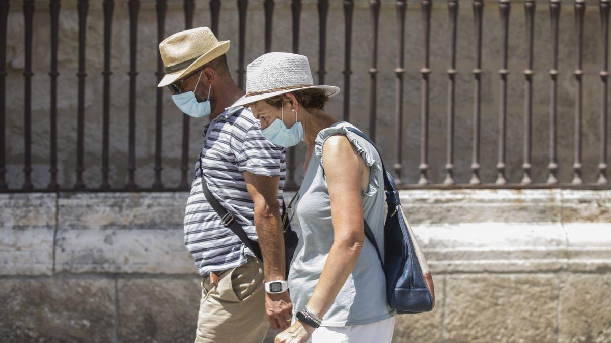 Dos personas caminan con mascarillas por la calle.