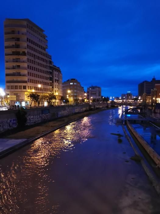 Inusual imagen, en Málaga capital, del cauce del Guadalmedina cubierto por el agua.