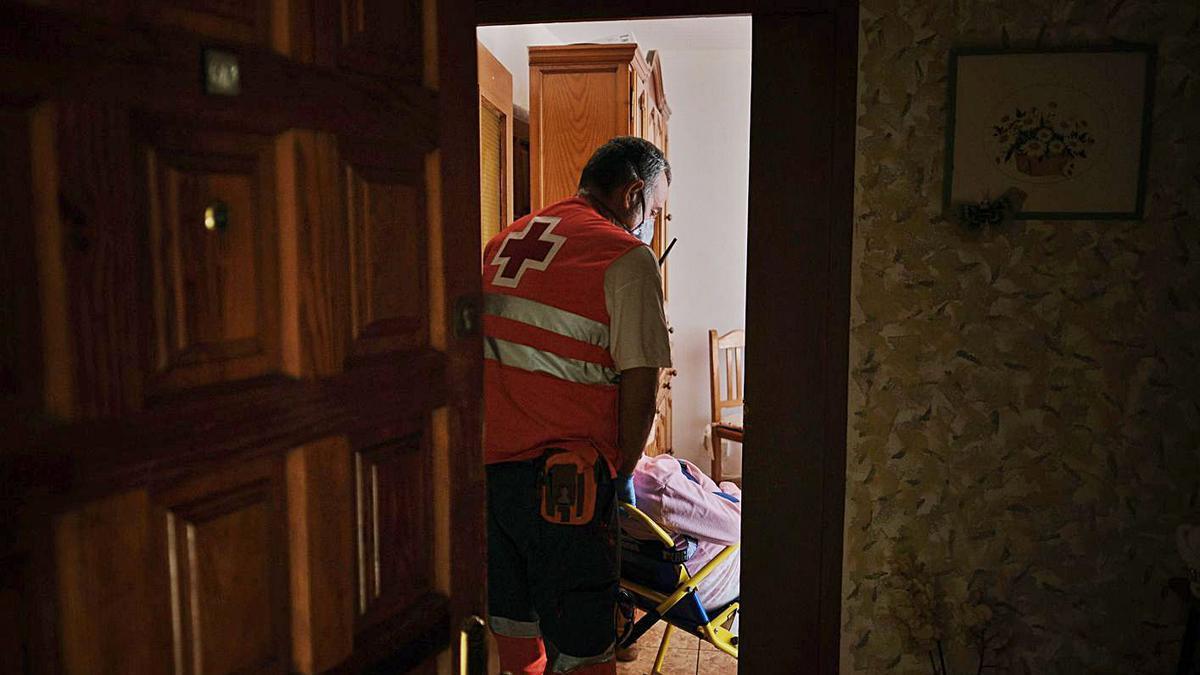 Un voluntario de Cruz Roja ayuda a trasladar a una vecina a un centro de salud.