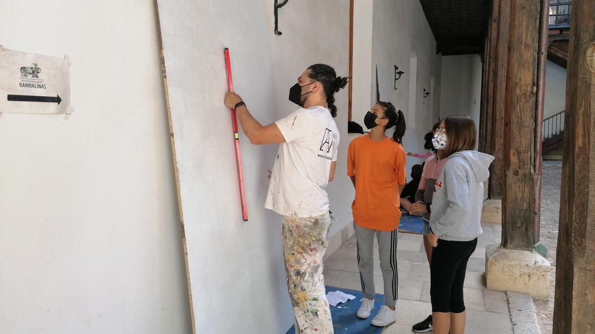 Varias jóvenes siguen con atención las indicaciones de Adeva en el proceso creativo de un mural