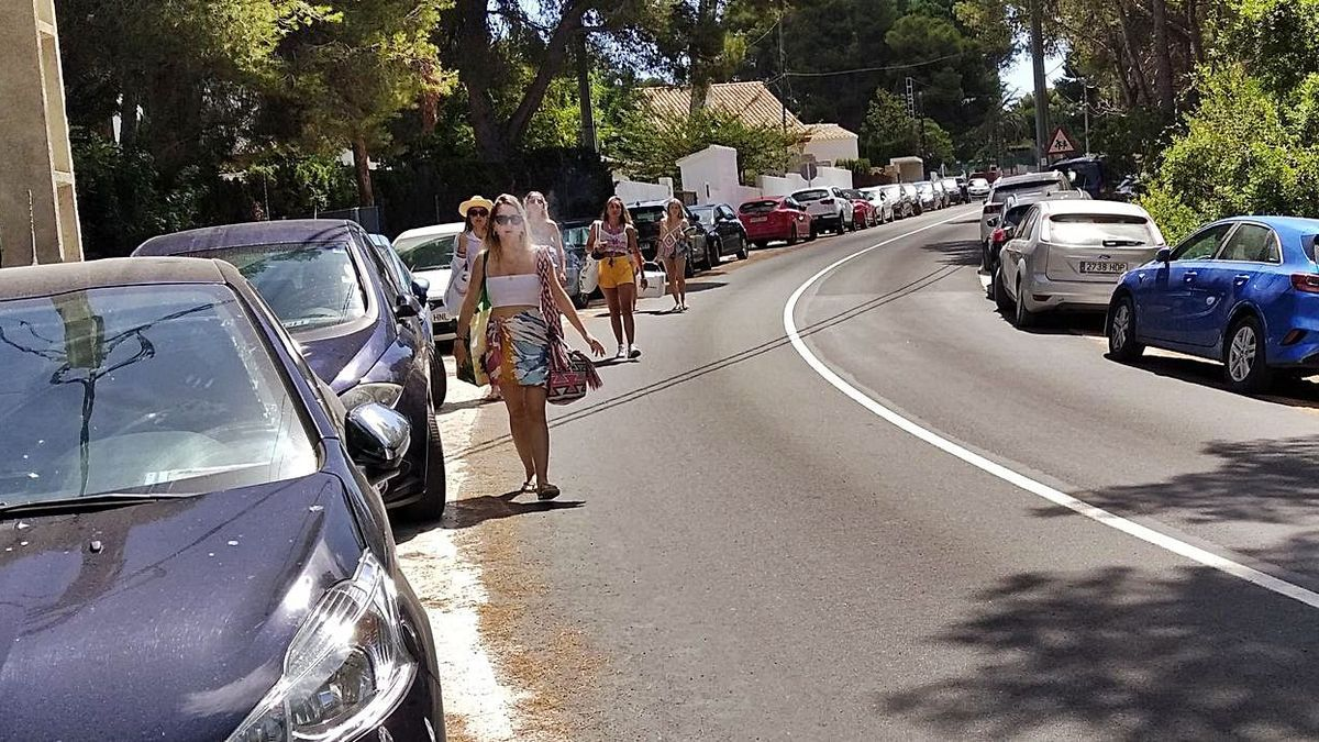 Bañistas caminando por la carretera del Portitxol, donde los coches invaden ambas cunetas.   A. P. F.