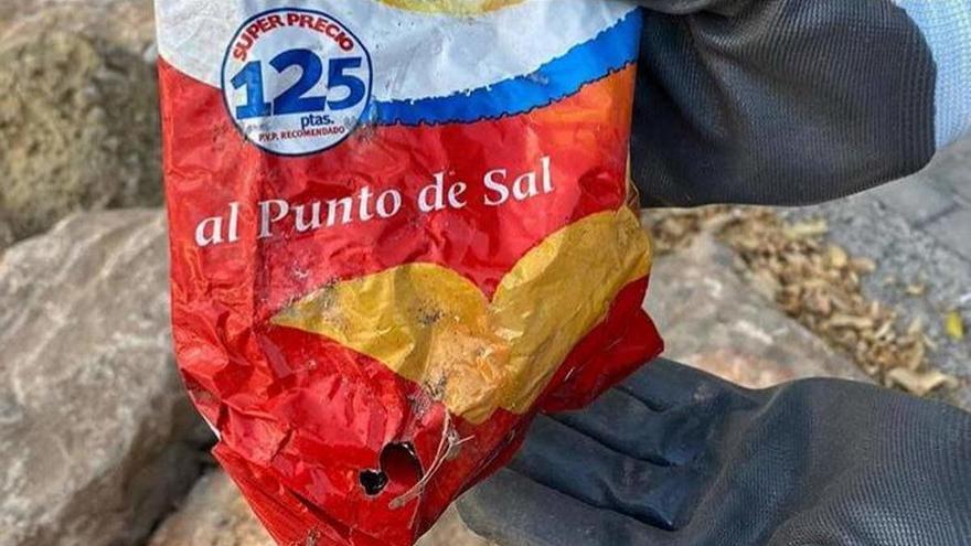 Hallan en las rocas de una playa valenciana una bolsa de patatas de más de 22 años