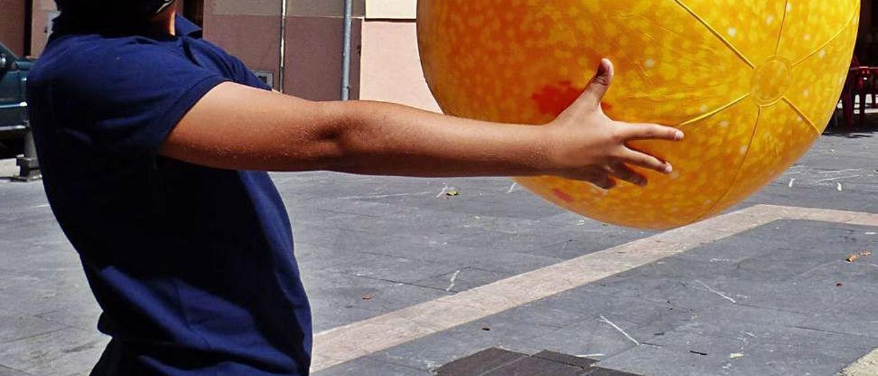 Orestes López, sujetando la pelota que identifica al sol, ayer, en Pola de Allande, durante la recreación a escala del sistema solar.