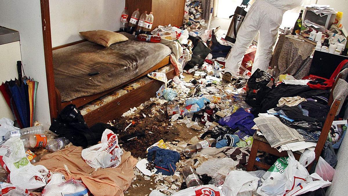 Un trabajador limpia la vivienda de una persona con síndrome de Diógenes.     // JORGE SANTOMÉ