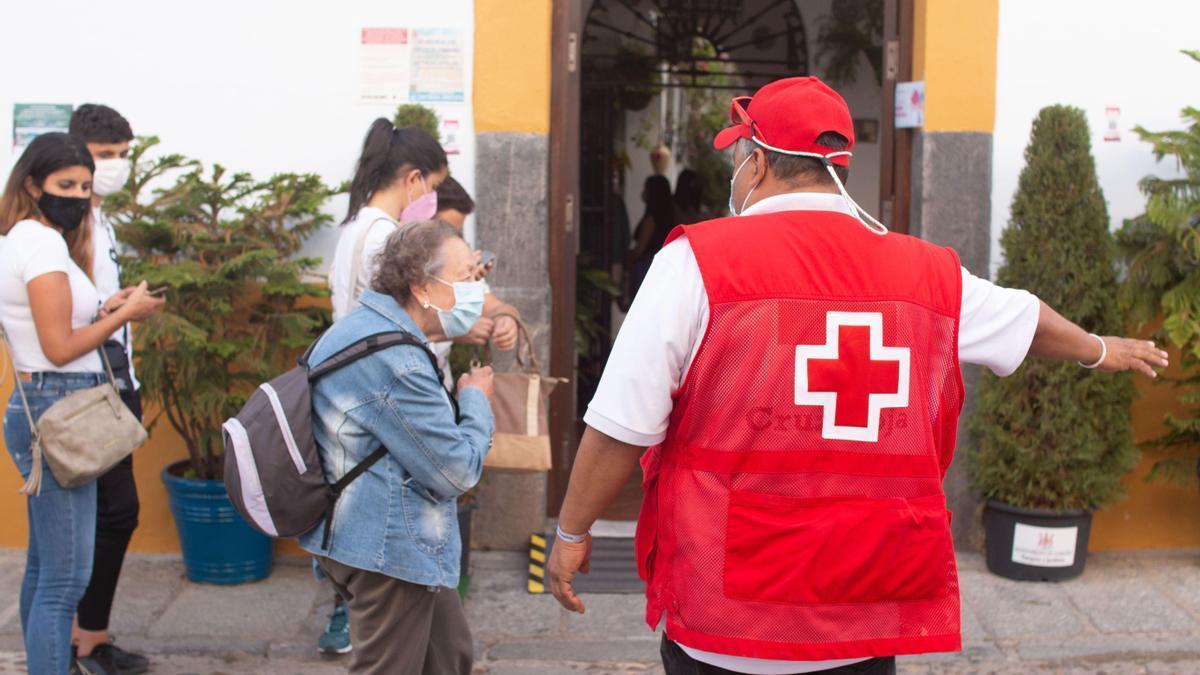 Un voluntario de Cruz Roja da indicaciones a los visitantes a la entrada de un patio.