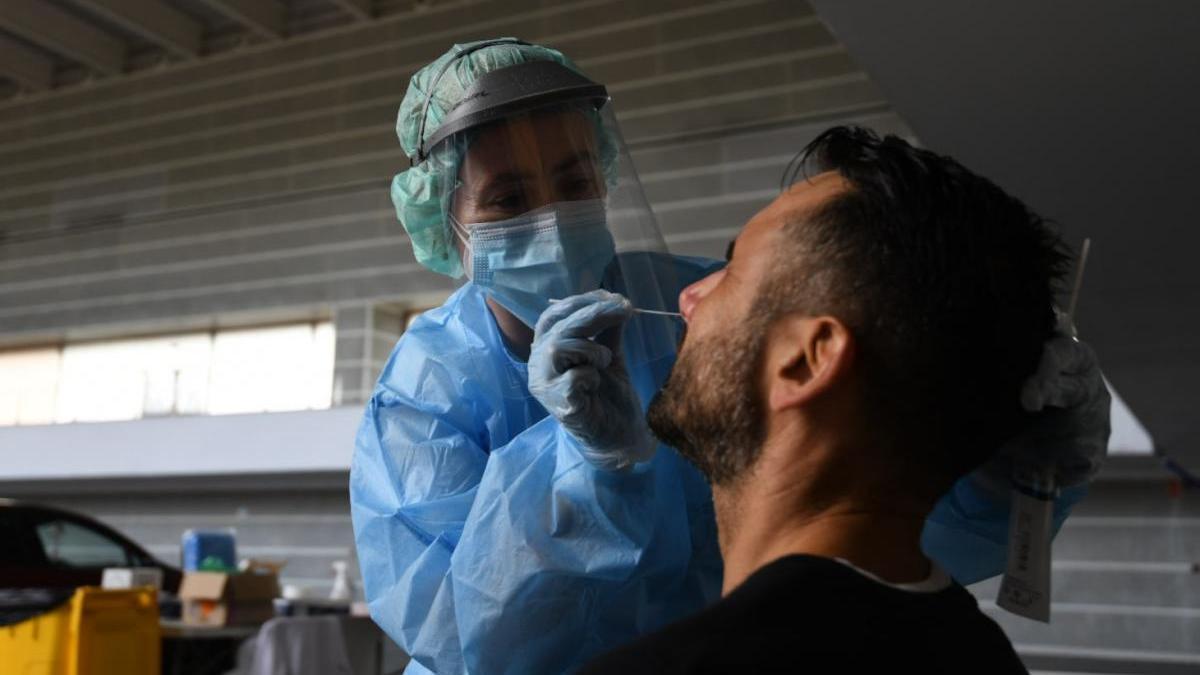 Una enfermera realizar una PCR a un hombre, esta mañana en el Recinto Ferial. // G. Santos