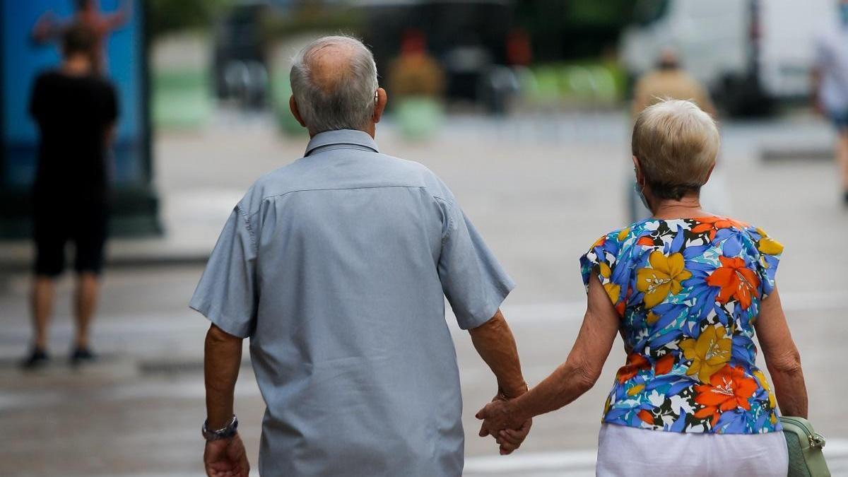 Una pareja de ancianos camina por la plaza del Ayuntamiento de València agarrada de la mano y con mascarilla.